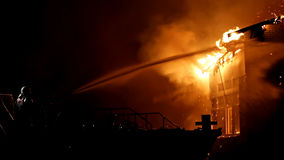 House on fire. Conflagration. Fireman fights fire. stock photo
