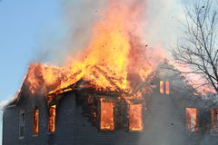House on fire. The house is engulfed in flames with debris flying out of the fire as the fire department burns and abandoned house for drill Royalty Free Stock Photo