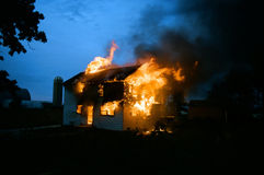 House on Fire. Home fully ablaze with flames leaping from roof, windows and door set against a twilight sky Stock Photo