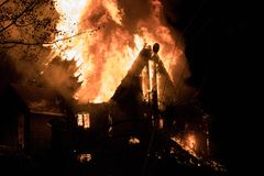 House fire with intense flame, fully engulfed house fire. House fire with intense and large flame, fully engulfed house fire stock photography