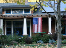 House with flag. House with an American flag hanging from the front porch Stock Images