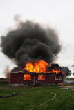 House in flame. Abandoned house in flame with firefighters in action Stock Images