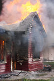 House in flame. Abandoned house in flame with firefighters in action Royalty Free Stock Photography