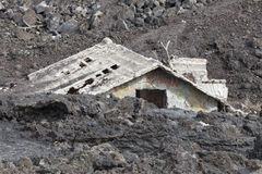 House flooded under the lava. A house flooded by lava. A house of two floors destroyed by the lava flow on Mount Etna, Sicily. Italy Stock Photos