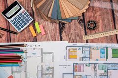 House floor paper plan and wooden sampler, work tolls, calculator. On wooden table royalty free stock photo