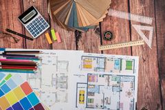 House floor paper plan and wooden sampler, work tolls, calculator. On wooden table stock photo