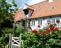 House with flower landscaping. Quaint country house with pretty flower landscaping and gate Stock Photo