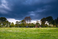 House on flowering meadow during storm Stock Images