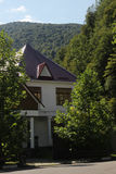 House at the foot of the mountains. Family nest, the family estate, the house near the mountains, surrounded by trees Royalty Free Stock Photo
