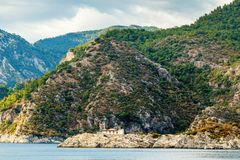 A house at the foot of a rocky shore in the Aegean Sea. The hous. E seems small in contrast with a large cliff Royalty Free Stock Photos