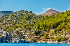 A house at the foot of a rocky shore in the Aegean Sea. The hous. E seems small in contrast with a large cliff Stock Photos