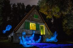 House in the forest illuminated with lanterns royalty free stock photography