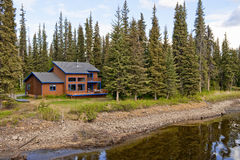 House in forest by river Royalty Free Stock Photo