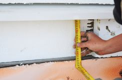 House foundation insulation with styrofoam thermal insulation board. Contractor hand with measure tape. House foundation insulation with styrofoam thermal stock image