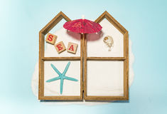 House frame with blue star fish and red umbrella Stock Photos