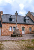 House in the French brittany. House  in the French brittany with courtyard and cross on a cloudy day. It´s a vertical picture Stock Image