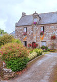 House in the French brittany. House  in the French brittany with path and flowers on a cloudy day. It´s a vertical picture Stock Photos