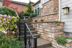 House Front Entry Concrete Stairs Stone Wall Planters. House front entry with concrete stairs iron rod railings stone wall planter siding by frontyard garden stock photos