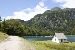 House in front of a lake and mountains Royalty Free Stock Photo