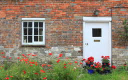 House front with red poppy flowers and geraniums Royalty Free Stock Photo