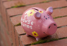 House funds piggy bank. On a wall Stock Photos