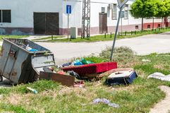 House furniture dumped in the garbage on the street in the city near metal dumpster junk can.  stock image