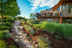 House and garden with creek. A view of a house and garden with terrace and creek Royalty Free Stock Image