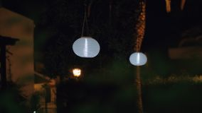 Garden with white Chinese lanterns at night. House garden at night with white Chinese paper lanterns hanging in the trees and illuminating in darkness stock video footage
