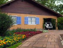 House in garden. View of mountain home with car garage surrounded by green grass, trees and gardens in summer - Gramado - Rio Grande do Sul - Brazil Stock Photos