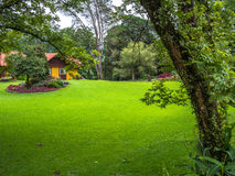 House in garden. View of mountain home surrounded by green grass, trees and gardens in summer - Gramado - Rio Grande do Sul - Brazil Royalty Free Stock Image