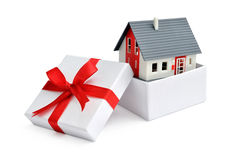 House in gift box. Model of a house in gift box with red ribbon Stock Photo