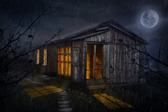 House with glowing windows at night. Rural house with glowing windows at night sky with moon Royalty Free Stock Photo