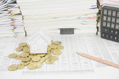 House on gold coins have paperwork with books as background Royalty Free Stock Images