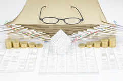House between gold coins have spectacles on top of envelope Stock Photos