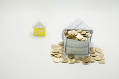 House of gold coins and little house. On white background stock photos
