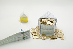 House of gold coins and pile overload document. With colorful paperclip and little house on white background Royalty Free Stock Image