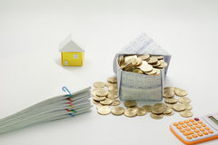 House of gold coins and pile overload document of report. With colorful paperclip with calculator and little house have blur on white background Royalty Free Stock Image