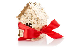 house of gold color puzzles with red bow Stock Photos