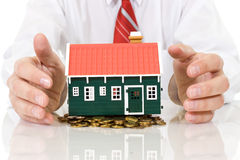 House on golden coins pile with businessman hands Stock Photos