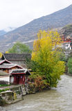 House with golden trees in fall. Sweet home with golden trees in fall, which is standing by river. Taken in Songpan, which is a small minority town and a Stock Photo