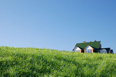 House and grass. Roof of house behind a hill Royalty Free Stock Photos