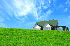 House and grass. House behind a green hill Stock Photography