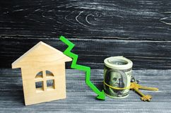 House with green arrow down. a decline in property prices. low energy efficiency, falling interest on the mortgage. reduction in d. Emand for the purchase of royalty free stock images