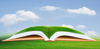 House on green field above open book. Use for housing and real estate theme Royalty Free Stock Photography