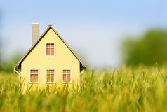 House in green grass over blue sky. Mortgage Stock Photos