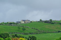 House on green hills in Ireland Stock Photos