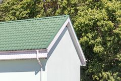 House with green tiled metal roof and white rain gutter on trees stock photo