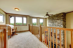 House hallway with stone fireplace and wood railing. House upstairs hallway with stone fireplace and wood railing Stock Photos