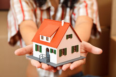 House in hand. Model house in woman's hand, boxes in the background Stock Images
