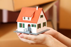 House in hand. Model house in woman's hand, boxes in the background Stock Photos